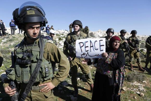 A protester holds a placard as she stands next to Israeli soldiers during a protest against Israeli settlements in Beit Fajjar town south of the West Bank city of Bethlehem