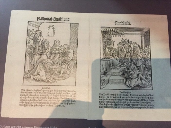 Christ washing feet and Pope having feet kissed.  Christ and Anti-Christ